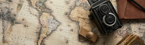 top view of vintage camera and stamp on map background, panoramic shot