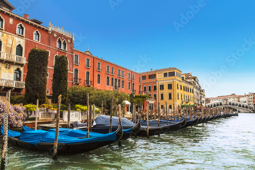 View of the Grand canal, pier with gondolas and Rialto bridge on the horizon, Venice, Italy