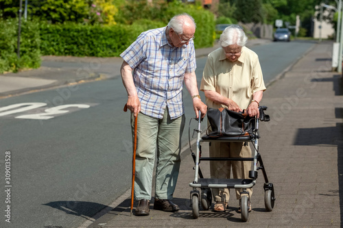 Elderly Couple with Walking Frame and Stick on the Sidewalk Wallpaper Mural