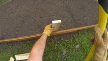 Home Gardening - Slow Motion Of Man Using Ax Back Side To Secure Wooden Post To Support Small Short Fence Or Garden Bed Border. View From First Person Perspective, Wide Angle Lens