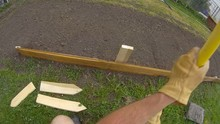 Home Gardening - Slow Motion Of Man Using Ax Back Side To Strike And Secure Wooden Post To Support Small Short Fence Or Garden Bed Border. View From First Person Perspective, Wide Angle Lens