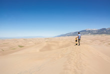Young Man With Sand Board On Sand Dune In Great Sand Dunes National Park Colorado