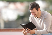 Happy Man Reading An Ebook Sit...