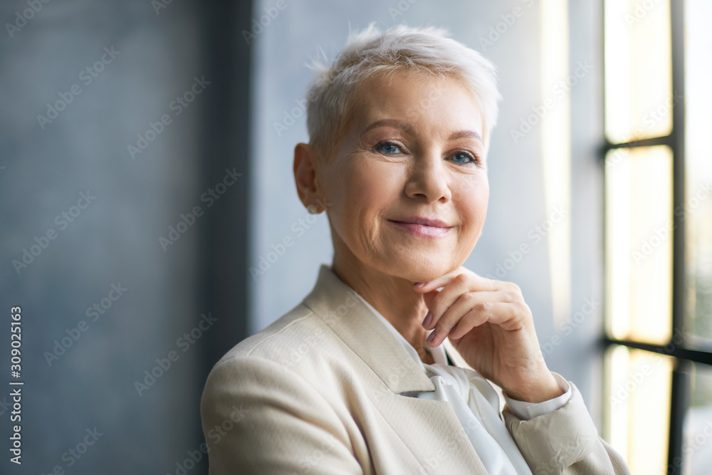Fototapeta Style, feminism, aging and employment concept. Fashionable blonde female in stylish suit achieving career goals being in mature age holding hand under her chin, her look expressing confidence