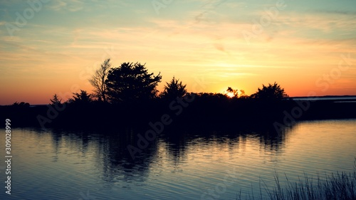 Sunset over Assateague Island over marshes, salt water bay with silhouette Fototapet