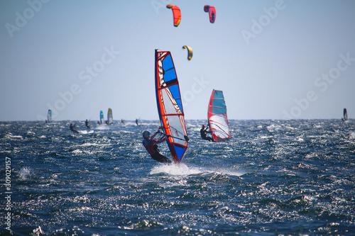 Windsurfers and kitesurfers on choppy sea, in backlight Canvas