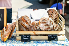 Closeup Of Fresh Traditional Baked Sourdough Bread Loaves In Bakery With Signs For Pain Au Levain And Honey Whole Wheat With Prices In Farmers Market