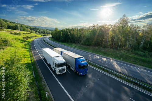 Blue truck overtaking white truck on an asphalt highway between forests under radiant sun Tapéta, Fotótapéta