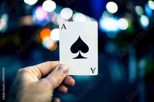 Fotomural  Ace Of Spades Playing Card In Cool Urban Setting Held By Hand Up Close Street Ma