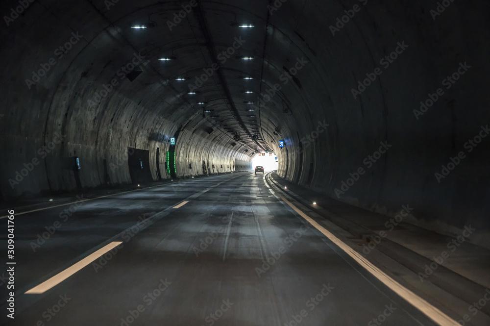 Fototapeta Fahrt durch einen dunklen Tunnel einer Autobahn mit Sicht auf das Licht am Ende des Tunnels