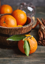 Fresh Tangerines Clementine With Green Leaves In Wooden Basket With Cinnamon On Old Wooden Board In Rustic Style.