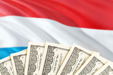 Luxembourg Economy Concept. Dollar Banknotes On The Side Of National Flag With Waving Background. Financial Theme.
