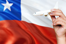 Chile Travel Concept. Woman Holding A Miniature Plane On National Flag Background. Holiday And Voyage Theme With Copy Space For Text.