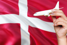 Denmark Travel Concept. Woman Holding A Miniature Plane On National Flag Background. Holiday And Voyage Theme With Copy Space For Text.