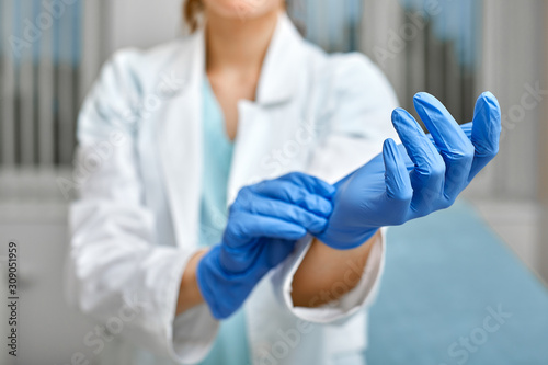 Photo Close up of a female doctor putting a blue latex gloves on a clinic background