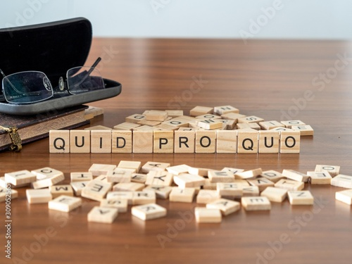 Photo quid pro quo the word or concept represented by wooden letter tiles