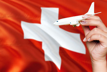 Switzerland Travel Concept. Woman Holding A Miniature Plane On National Flag Background. Holiday And Voyage Theme With Copy Space For Text.