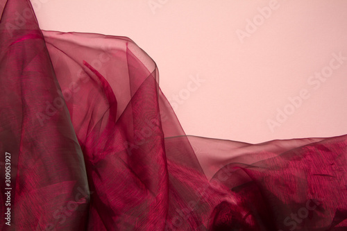 Obraz na plátně Falds of red fabric tulle or organza on a coral color background, selective focu