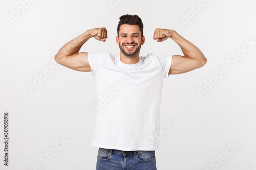 Carta da parati Handsome fit young funny bearded man pointing to his bicep and smiling on white
