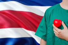 Costa Rica Veterinary Clinic Concept. Veterinarian Is Holding Plastic Heart In Green Uniform On National Flag Background. Animial Love Theme.