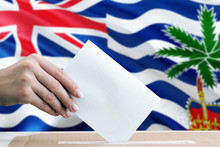 British Indian Ocean Territory Election Concept. Side View Woman Putting A Ballot In A Box On National Flag Background.