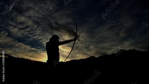 Fotomural Die Silhouette eines Bogenschützen bei Sonnenuntergang