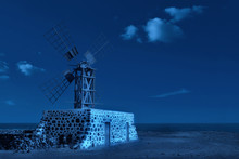 Classic Blue Monochrome Toned Image Of Traditional Windmill At Night With Moonlight By The Ocean. Fuerteventura, Canary Islands, Spain.