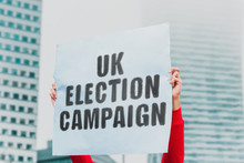 "The Phrase "" UK Election Campaign "" On A Paper Banner In Men's Hand. Human Holds A Cardboard With An Inscription. Politics. Protest. Election. United Kingdom. Crisis"