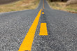 low angle closeup view of yellow dividing and no passing lines and stripes in middle of asphalt road