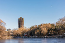 Historical Boya Pagoda Or Tower By Frozen Weiming Lake In Winter With The Moon Over Blue Sky In Peking University, Haidian, Beijing, China.