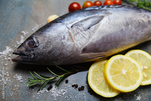 Photo Fresh fish with herbs spices rosemary tomato and lemon - Raw fish seafood on bla