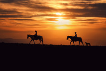 Two Horse Riders In Front Of A Beautiful Sunset With A Dog Trailing Behind