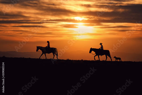 Fotografiet two horse riders in front of a beautiful sunset with a dog trailing behind