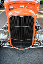 Vintage Orange Retro Car With A Large Grille And An Open Wheel Suspension And Headlights On The Sides Of The Body At A Street Exhibition Of Old Cars