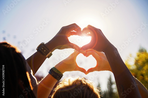 Fototapeta beautiful photo of a couple making heart shapes with their hands toned with a re