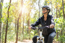 Senior Asian Woman Riding Bikes In Park