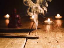 Smoking Incense Stick In The Foreground. On Background Small Statue Of Buddha With Incense Sticks And Burning Candles