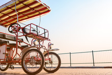 Four-wheeled Red Bike For Rent With An Awning And A Wheel Stands On The Promenade Against The Sun. Eco-friendly Street Transport.