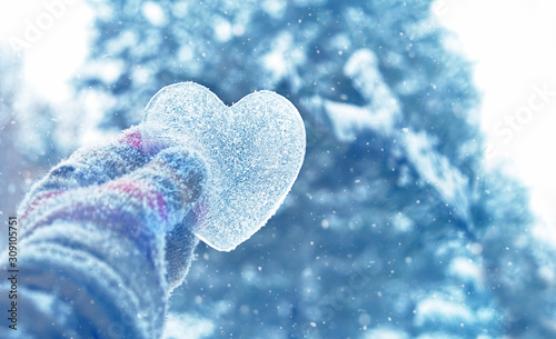icy heart in hand. concept of love, romantic, February 14, Valentine\'s day, winter season holiday. atmosphere winter image. frozen heart. copy space