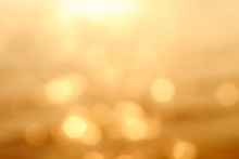 Delicate Golden Texture Bokeh Background. Blurry Yellow Bokeh Glare On The Water During Sunset And Dawn