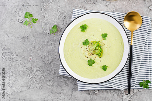 Fotografiet Homemade broccoli cream soup with croutons in white bowl on grey background