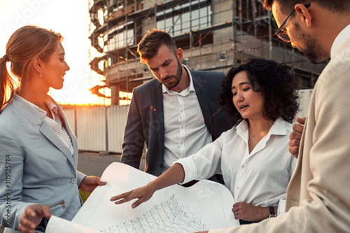 Fototapety, obrazy: Business partners discussing a blueprint in front of the construction site.