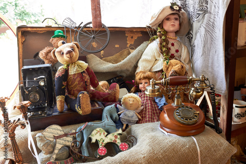Fotografie, Obraz Suitcase with toys and dolls (Teddy bear) and a vintage telephone