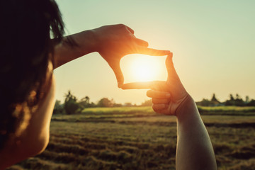 woman hand framing view distant over sunset. business concept