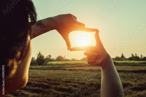 woman hand framing view distant over sunset. business concept Canvas Print