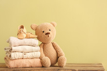 Stack Of Baby Clothes And Toy On Table