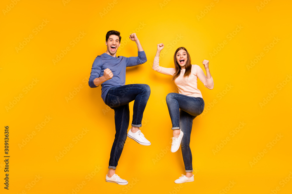 Fototapeta Full size photo of ecstatic married spouses hear wonderful lottery win news raise fists scream yeah wear pink blue sweater sneakers isolated over shine color background