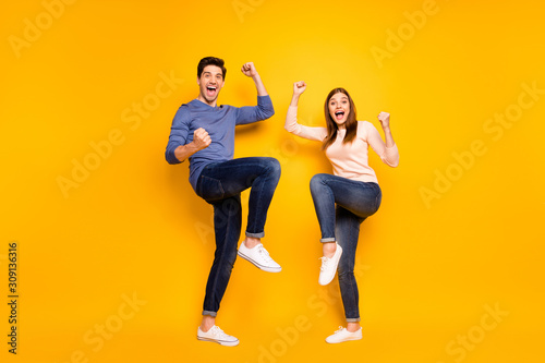 Full size photo of ecstatic married spouses hear wonderful lottery win news raise fists scream yeah wear pink blue sweater sneakers isolated over shine color background