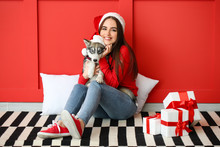 Cute Woman With Funny Husky Puppy And Christmas Gifts Sitting Near Color Wall