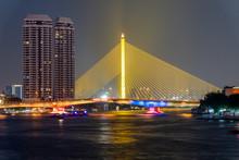 The Illuminated Colorful Somdet Phra Pinklao Bridge And Rama VIII Bridge Crossing Bangkok, Thailand's Chao Phraya River At Night.